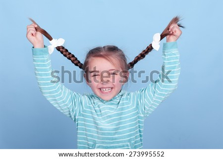 Laughing kid girl 3-4 year old having fun over blue. Wearing blue striped hoodie. Holding braids. Smiling baby.  - stock photo