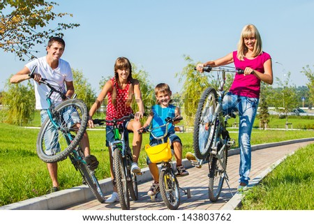 Laughing kids and their parent with bicycles - stock photo