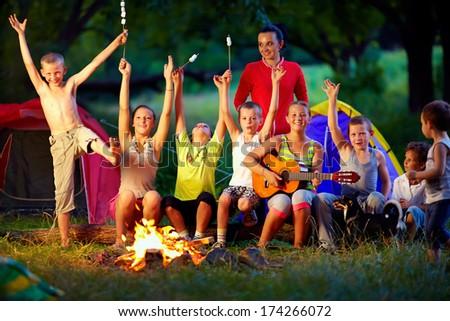 laughing kids friends having fun around campfire - stock photo