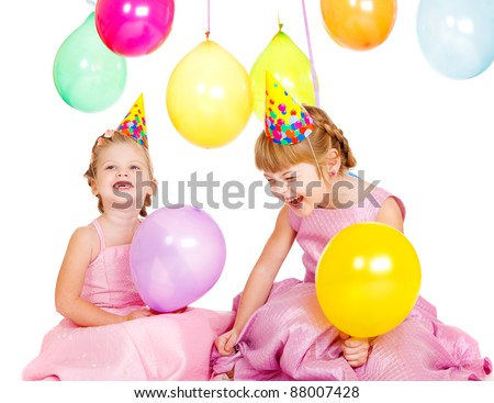 Laughing kids in party hats playing with birthday balloons - stock photo