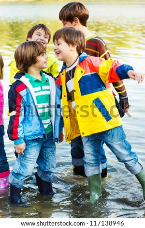 Laughing kids stand in water - stock photo