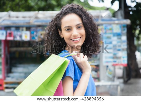 Laughing latin american woman with shopping bags - stock photo