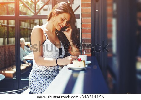 Laughing latin woman with luxurious figure talking on her smart phone while sitting at sidewalk cafe in summer, young female breakfast with cup of cappuccino and cake while have cellphone conversation - stock photo