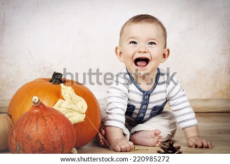 Laughing little baby sitting on the floor with pumpkins - stock photo