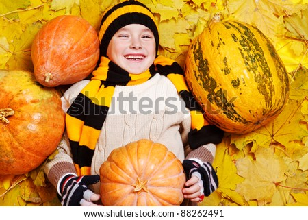 Laughing little boy in hat and scarf lying on yellow autumnal leaves - stock photo