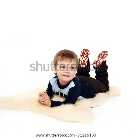 Laughing little boy laying on floor - stock photo