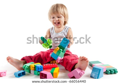 Laughing little boy playing with colorful blocks, isolated on white background - stock photo