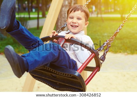 laughing little boy riding on a swing and looking at camera in a park - stock photo
