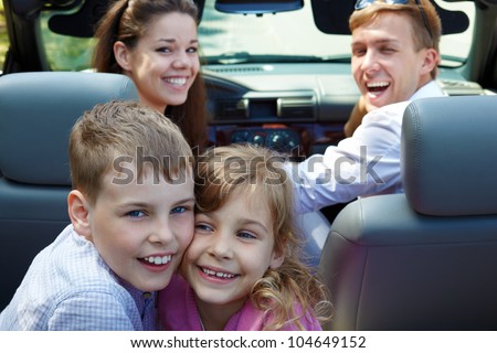 Laughing little brother and sister sit on back seat of open top car, nestling with their cheeks, on front seats - young laughing couple - stock photo