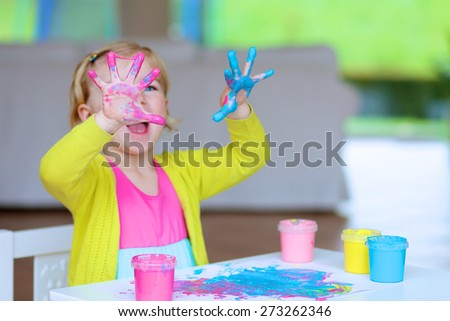 Laughing little child, blonde artistic toddler girl painting and drawing with colorful finger paints indoors at bright room at home or kindergarten. Focus on messy hands - stock photo