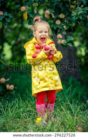 Laughing little girl holding apples in the garden - stock photo