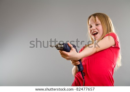 Laughing little girl holding electric drill - stock photo