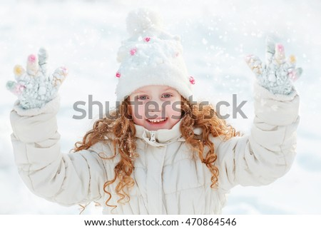 Laughing little girl on a winter walk on clouds sky background.