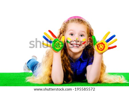 Laughing little girl painted in bright colors lying on green grass. Happy childhood.