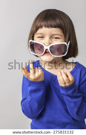 laughing little girl playing with huge sunglasses on her nose like a mask - stock photo