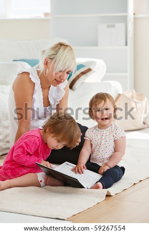 Laughing little girl using a laptop with her family at home - stock photo