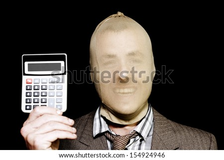 Laughing male robber wearing a stocking mask holding up a portable mathematical calculator in a Cost of Crime concept isolated on black background - stock photo