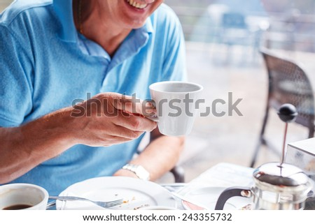 Laughing man have a lunch time and drinks his coffee - stock photo