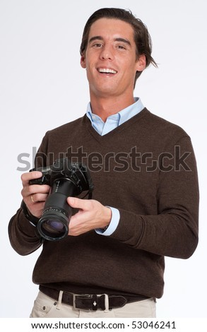 Laughing man in brown holding a photo camera - stock photo