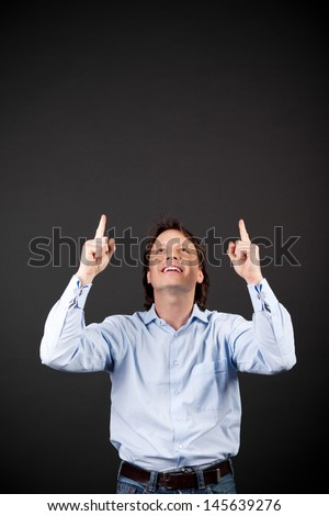 Laughing man pointing above himself to blank copyspace on a dark studio background - stock photo