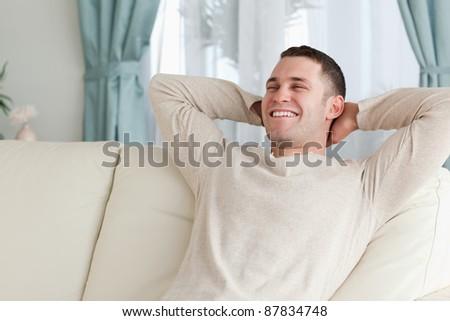 Laughing man relaxing on a sofa in his living room
