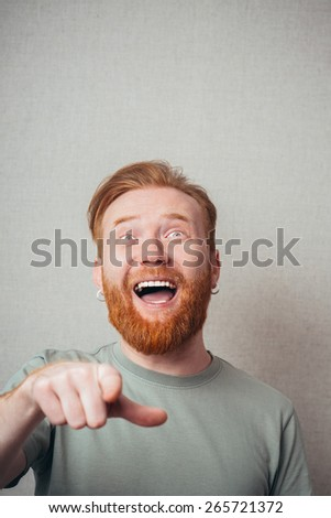 Laughing man with beard pointing at camera - stock photo