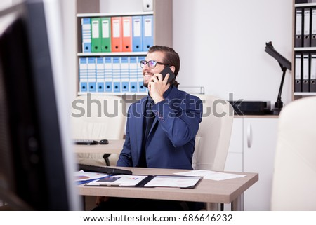 Laughing Manager with a smartphone in hands in his modern office. Image of successful businessman in blue suit. Communication and technology