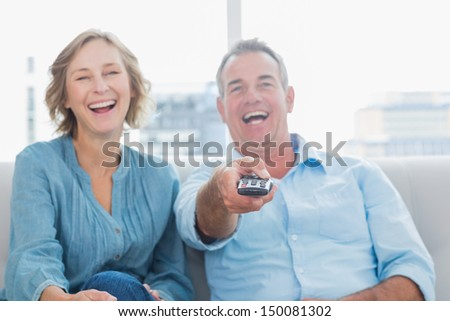 Laughing middle aged couple sitting on the couch watching tv at home in the living room