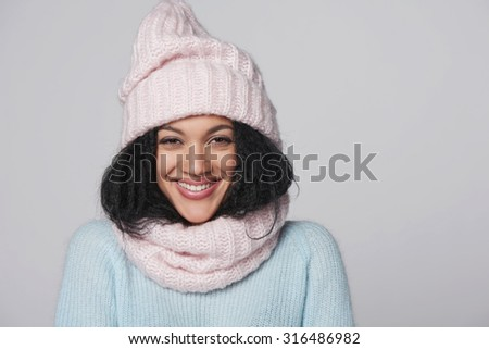 Laughing mixed race african american - caucasian girl wearing knitted sweater and hat with scarf, over gray background - stock photo