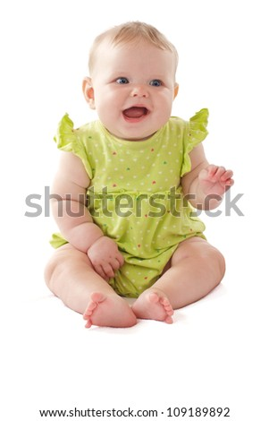 Laughing 6 month old baby girl wearing a lime green dress sits and waves her arms. Pastels, isolated on white background, vertical, copy space.