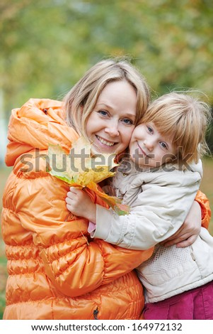 Laughing mother and daughter in autumn park - stock photo