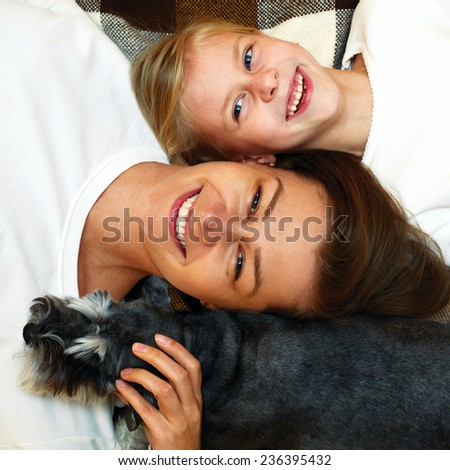 laughing mother and daughter lying together on the plaid