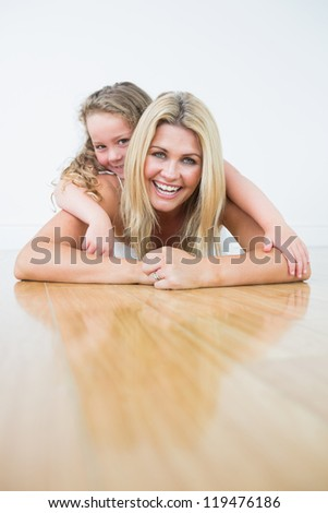 Laughing mother and daughter resting on the floor - stock photo
