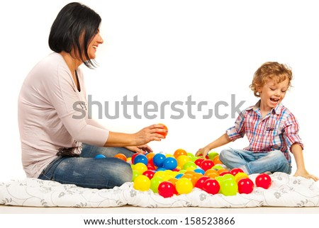 Laughing mother and son playing home with balls isolated on white backgroun