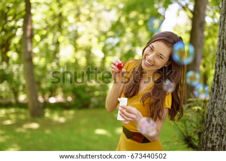 Laughing playful woman blowing soap bubbles as she relaxes outdoors in a shady leafy green garden or park