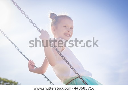 Laughing pretty girl on swing in summer beach park
