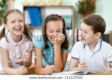 Laughing pupils help to each other to do the task - stock photo