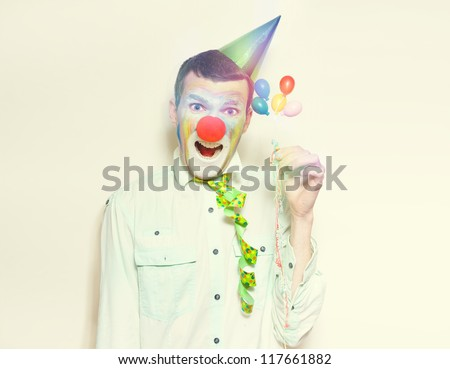 Laughing Retro Clown Holding Celebration Balloons And Streamers While Celebrating A Happy Birthday - stock photo