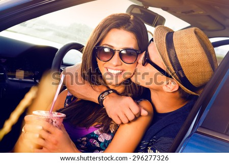 Laughing Romantic teenage hikers couple sitting on the hood of their car while out on a road trip.woman kissing boyfriend,smiling,outdoors.teen,purse,hat,Couple having fun on road trip on a summer day - stock photo