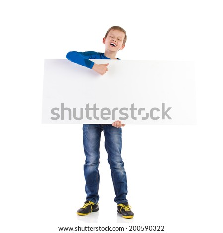 Laughing schoolboy holding white blank banner and showing thumb up. Full length studio shot isolated on white. - stock photo