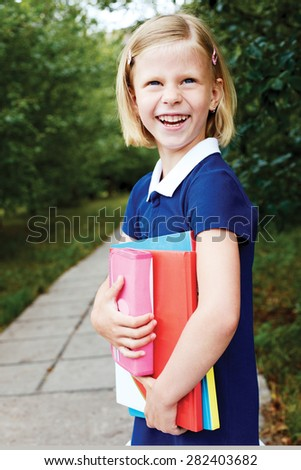 Laughing schoolgirl standing at the blackboard and holds in hands textbooks.