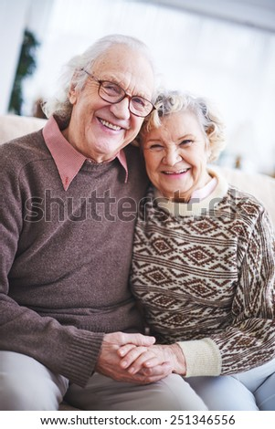 Laughing senior couple in sweaters looking at camera - stock photo