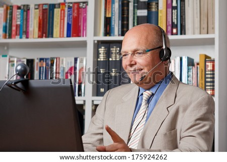 Laughing senior employee telephoning by means of computer, webcam and headset - stock photo