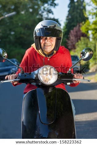 Laughing senior woman riding a scooter peering over the handlebars at the camera from under her helmet - stock photo
