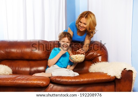 Laughing son eating popcorn and happy mother - stock photo