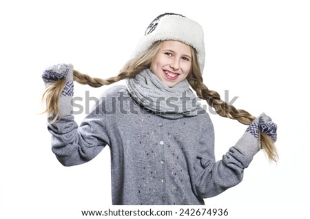 Laughing teen girl with long braids in warm hat and mittens - stock photo