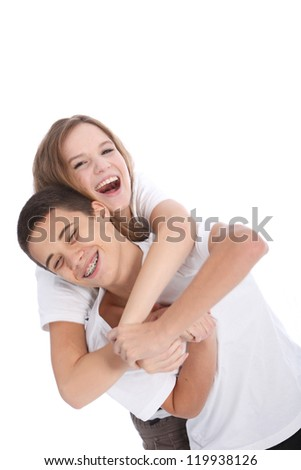Laughing teenage brother and sister having fun together fooling around mock wrestling isolated on white - stock photo
