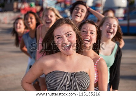 Laughing teenage friends behind one another outside - stock photo