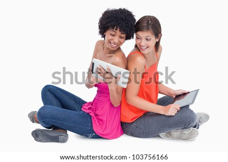 Laughing teenagers looking at a tablet computer while sitting with their leg crossed - stock photo