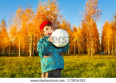 Laughing three years old little boy throw white volleyball ball autumn park - stock photo